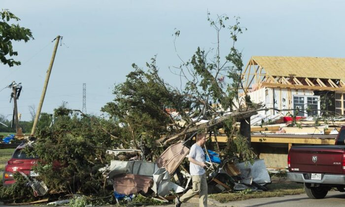 A man surveys the damage after a tornado touched down in Mascouche, Que., northeast of Montreal, on June 21, 2021. Dozens of homes were damaged and one death has been confirmed. (The Canadian Press/Ryan Remiorz)
