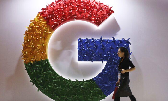 A woman walks past the logo for Google at the China International Import Expo in Shanghai, on Nov. 5, 2018. (Ng Han Guan/AP Photo)