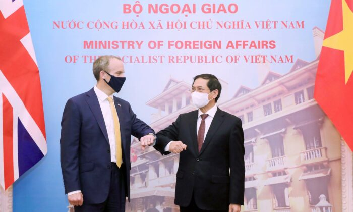 Britain's Foreign Secretary Dominic Raab, left, and Vietnamese Foreign Minister Bui Thanh Son greet with an elbow bump in Hanoi, Vietnam, on Jun. 22, 2021. (Bui Lam Khanh/VNA via AP)