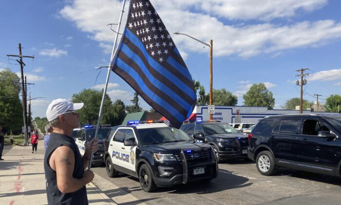 John Garrod, of Arvada, stands holding a blue line flag at the beginning of a line of about 30 police cars lined up for a procession in honor of the officer who was fatally shot in Arvada, Colo., on June 21, 2021. (Colleen Slevin/AP Photo)