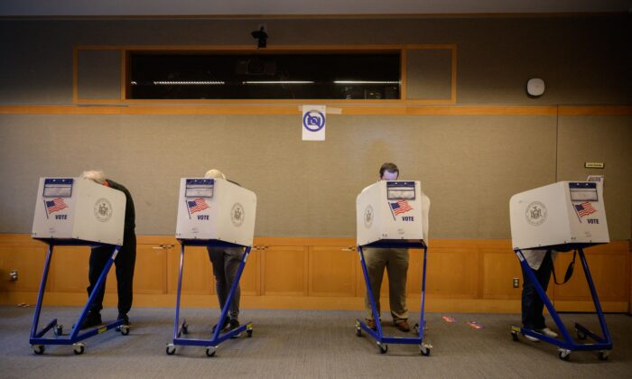 Voters stand in booths at a voting station at the Metropolitan Museum of Art during the mayoral election process in New York on June 12, 2021. (Ed Jones/AFP via Getty Images)