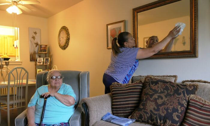 Martina Negron looks out a window as her home health aide Lidia Vilorio spends time cleaning, in Haverstraw, N.Y., on May 5, 2021. (Michael M. Santiago/Getty Images)
