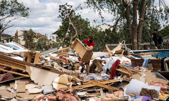 Dozens of volunteers help clean up a demolished home on Princeton Circle near Ranchview Drive in Naperville, Ill., after a tornado ripped through the western suburbs overnight, on June 21, 2021. (Ashlee Rezin Garcia/Sun-Times/Chicago Sun-Times via AP)