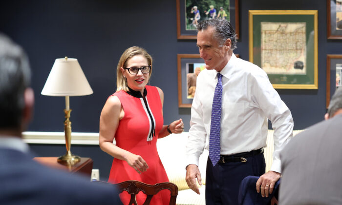 Sens. Kyrsten Sinema (D-Ariz.) (L) and Mitt Romney (R-Utah) arrive for a bipartisan meeting on infrastructure after original talks fell through with the White House in Washington on June 8, 2021. (Kevin Dietsch/Getty Images)