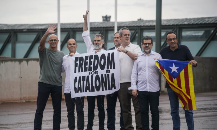 """Catalan leaders imprisoned for their role in the 2017 push for an independent Catalan republic, hold a banner and an """"estelada"""" or Catalan pro-independence flag outside Lledoners prison in Sant Joan de Vilatorrada, near Barcelona, Spain, on June 23, 2021. (Joan Mateu/AP)"""