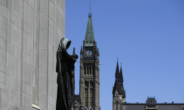 The sculpture of Ivstitia (Justice) at the Supreme Court of Canada is seen alongside the Peace Tower on Parliament Hill in Ottawa, on June 17, 2021. (The Canadian Press/Justin Tang)