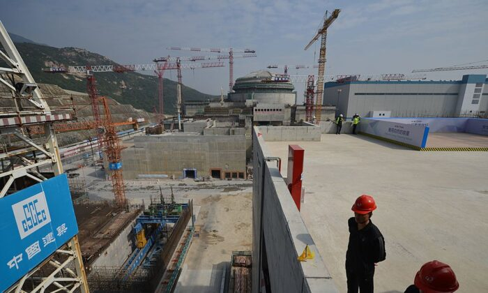 Workers wait for French Prime Minister Jean-Marc Ayrault to arrive at the joint Sino-French Taishan Nuclear Power Station outside the city of Taishan in Guangdong Province, China, on Dec. 8, 2013. French Prime Minister Jean-Marc Ayrault touted his country's nuclear expertise during his visit to China—the world's largest market for atomic power stations. (Peter Parks/AFP via Getty Images)