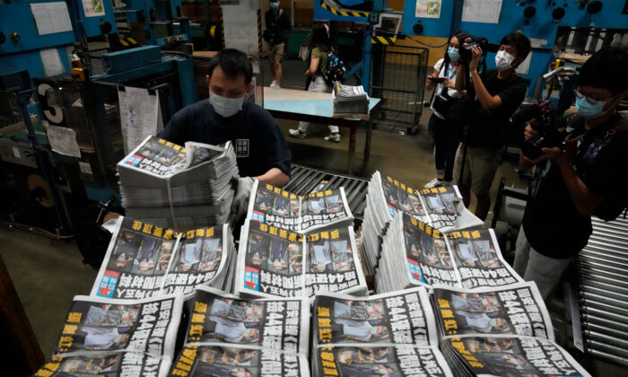 A worker packs copies of the Apple Daily newspaper at the printing house in Hong Kong on June 18, 2021. (AP Photo/Kin Cheung)
