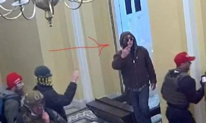 In this image from surveillance video, a man identified by law enforcement as Bryan Wayne Ivey holds a cellphone in front of him after entering the U.S. Capitol on Jan. 6, 2021. (DOJ)