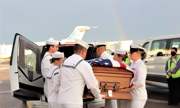 Navy Honor Guard from the Navy Operational Support Center in Louisville, Ky., place the remains of Scott Magers in a hearse as a rainbow glows overhead at Nashville, Tenn., International Airport on May 26, 2021 (James Perry)