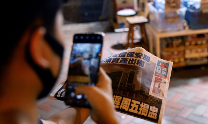 A man takes a photo of his copy of the Apple Daily newspaper after it looked set to close for good by Saturday following police raids and the arrest of executives in Hong Kong, on June 22, 2021. (Tyrone Siu/File/Reuters)