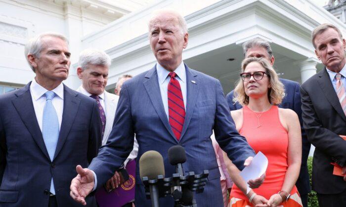 President Joe Biden (C), joined by from left to right, Sen Jeanne Shaheen (D-NH), Sen. Rob Portman (R-OH), Sen Bill Cassidy (R-LA), Sen. Kyrsten Sinema (D-AZ), Sen. Mark Warner (D-VA) and Sen Mitt Romney (R-UT), speaks after the bipartisan group of Senators reached a deal on an infrastructure package at the White House on June 24, 2021 (Kevin Dietsch/Getty Images)