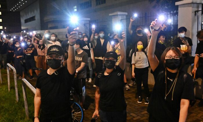 Supporters of Hong Kong newspaper Apple Daily wave their cellphone lights outside of the paper's headquarters in Hong Kong on June 23, 2021. (Sung Pi-lung/The Epoch Times)