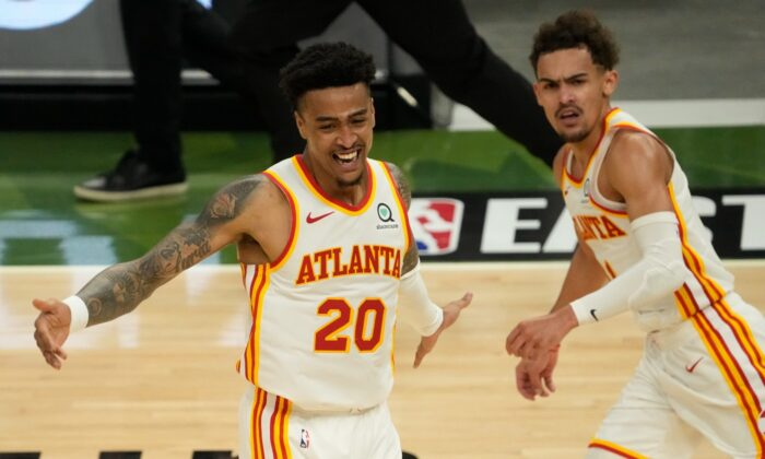 Atlanta Hawks' John Collins reacts after a dunk assisted by Trae Young during the second half of Game 1 of the NBA Eastern Conference basketball finals game against the Milwaukee Bucks, in Milwaukee, Wis., on June 23, 2021. (Morry Gash/AP Photo)