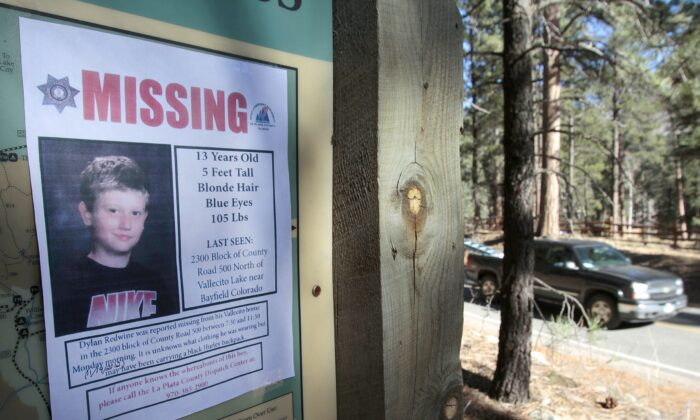 A missing poster of 13-year-old Dylan Redwine hangs on a trail head sign next to Vallecito Reservoir in Vallecito, Colo. on Nov. 26, 2012,(Shaun Stanley/The Durango Herald via AP)