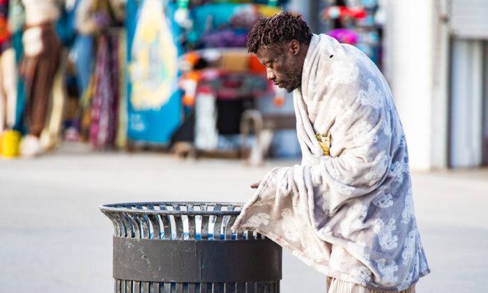 A homeless man looks for food in a trash can in Venice Beach, Calif., on Jan. 27, 2021. (John Fredricks/The Epoch Times)