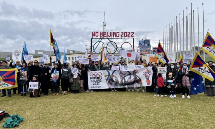 """Protesters holds up banners during the """"No Beijing 2022"""" rally outside Parliament House in Canberra, Australia, on June 23, 2021. (The Epoch Times)"""