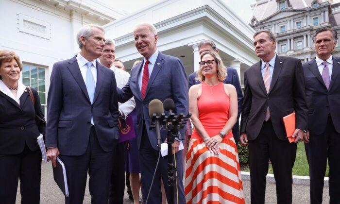 President Joe Biden (C), joined by from left to right, Sen. Jeanne Shaheen (D-NH), Sen. Rob Portman (R-OH), Sen. Bill Cassidy (R-LA), Sen. Kyrsten Sinema (D-AZ), Sen. Mark Warner (D-VA) and Sen. Mitt Romney (R-UT), speaks after the bipartisan group of Senators reached a deal on an infrastructure package at the White House on June 24, 2021 (Kevin Dietsch/Getty Images)