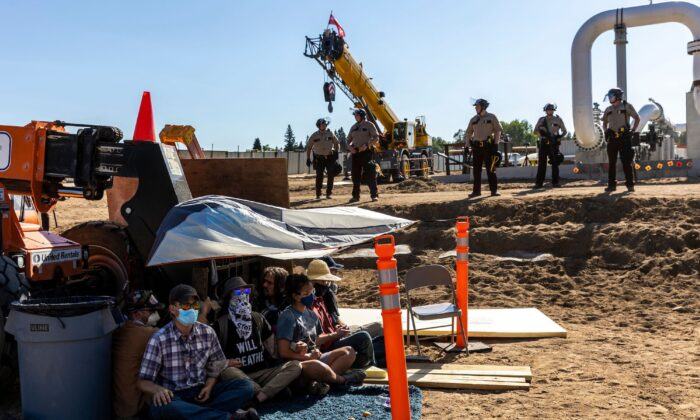 Environmental activists stage a sit-in in front of construction equipment as police stand by, at the Line 3 pipeline pumping station near Itasca State Park, Minn. on June 7, 2021. (Kerem Yucel/Getty Images)