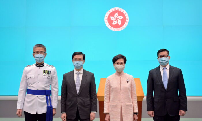 (L-R) New Commissioner of Police, Raymond Siu Chak-yee, Chief Secretary for Administration John Lee Ka-chiu and Secretary for Security Chris Tang Ping-keung pose for a photo with Chief Executive Carrie Lam after taking the oath of office in Hong Kong, China June 25, 2021. (Information Services Department/Handout via Reuters)