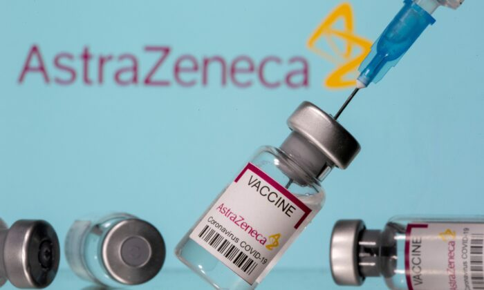 """Vials labelled """"Astra Zeneca COVID-19 Coronavirus Vaccine"""" and a syringe are seen in front of a displayed AstraZeneca logo, in this illustration photo taken on March 14, 2021. (Dado Ruvic/Illustration/Reuters)"""