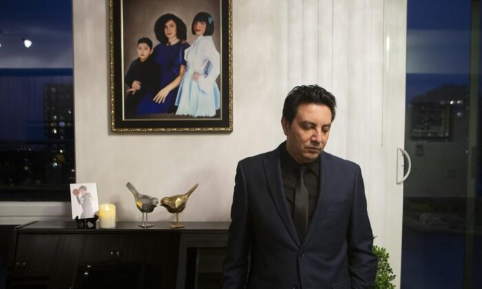 Alireza Ghandchi is photographed in front of a portrait of his wife Faezeh, daughter Dorsa and son Daniel in Richmond Hill , Ont., on January 1, 2021. Ghandchi lost his family after Iranian forces shot down a Ukrainian passenger jet on Jan. 8, 2020. (The Canadian Press/Chris Young)