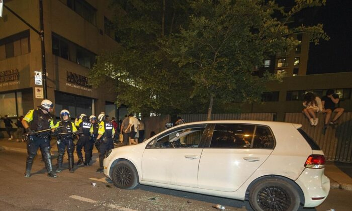 Police surround a car after it was vandalized as Montreal Canadiens fans celebrate on Rue René Lévesque after the Canadiens defeated the Vegas Golden Knights in overtime game 6 NHL Stanley Cup playoff hockey semifinal action in Montreal, on June 24, 2021. (The Canadian Press/Peter McCabe)