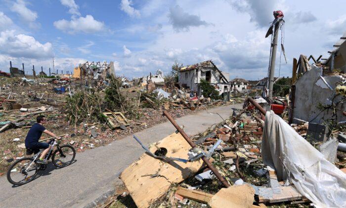 Man rides his bike after a tornado hit the village of Mikulcice in the Hodonin district, South Moravia, Czech Republic, on June 25, 2021. (Ondrej Deml/CTK via AP)