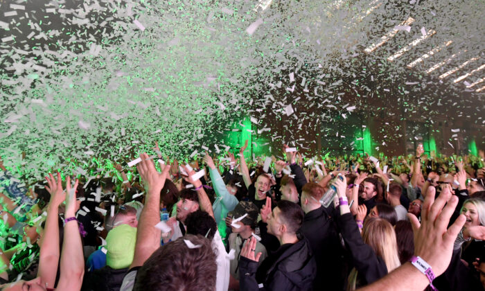 Confetti is fired into the crowd as Nightclub Circus hosts the first dance event, which will welcome 6,000 clubbers to the city's Bramley-Moore Dock warehouse in Liverpool, England,  on April 30, 2021.  (Anthony Devlin/Getty Images)