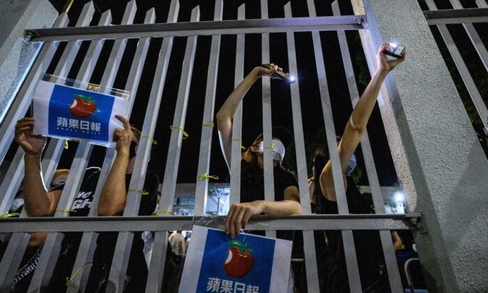 Supporters stand outside the main gate of the Apple Daily offices after the company's final newspapers were printed at the printing facility in Hong Kong early on June 24, 2021. (Anthony Wallace/AFP via Getty Images)