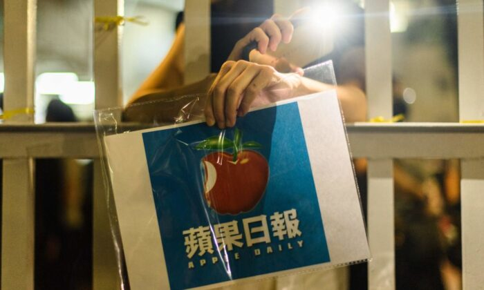 A supporter holds a poster of the Apple Daily newspaper logo outside the media company's office building in Hong Kong in the early hours of June 24, 2021, shortly after the 26 year old newspaper went to print for the last time. (Anthony Wallace/AFP via Getty Images)