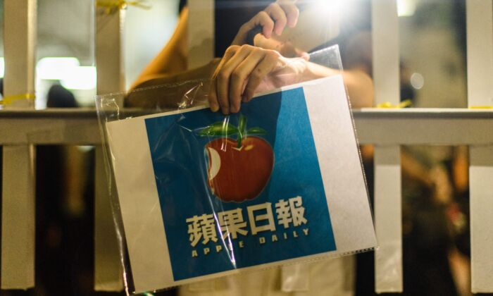 A supporter holds a poster of the Apple Daily newspaper logo outside the media company's office building in Hong Kong in the early hours of June 24, 2021. (Anthony Wallace/AFP via Getty Images)