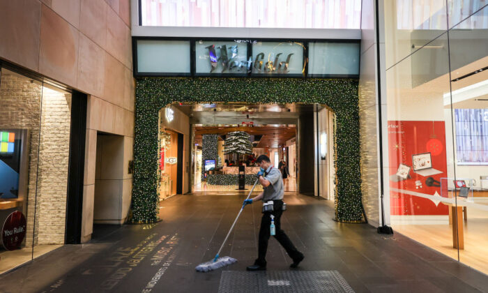 A cleaner works outside the entrance to the Westfield shopping centre during the Boxing Day sales on Dec. 26, 2020, in Sydney, Australia. (David Gray/Getty Images)
