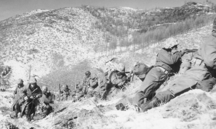 United States Marines infantrymen, taking cover behind large boulders, shoot at North Korean forces during a battle on a snow-covered mountain in the Korean War, Korea, on Dec. 6, 1950. The Marines won the battle, backed by close air support. (Hulton Archive/Getty Images)