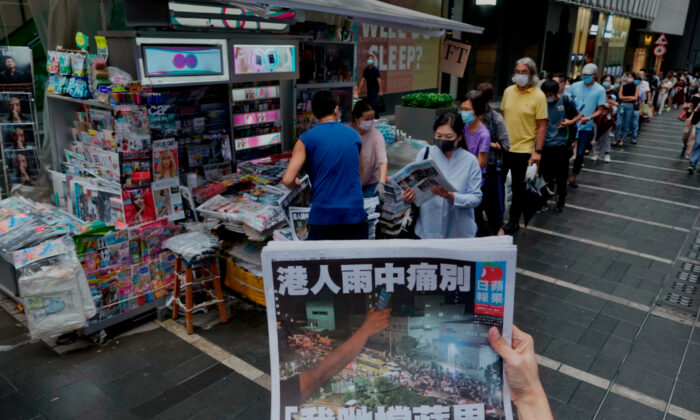 A woman tries to take a picture of last issue of Apple Daily in front of a newspaper booth where people queue up to buy the newspaper at a downtown street in Hong Kong, on June 24, 2021. (Vincent Yu/AP Photo)