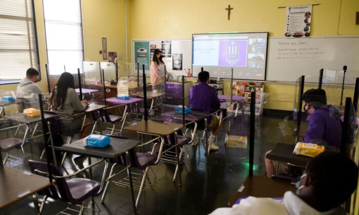 A teacher speaks with students in the classroom and online as they return to in-person learning at St. Anthony Catholic High School during the COVID-19 pandemic in Long Beach, Calif., on March 24, 2021. (Patrick T. Fallon/AFP via Getty Images)
