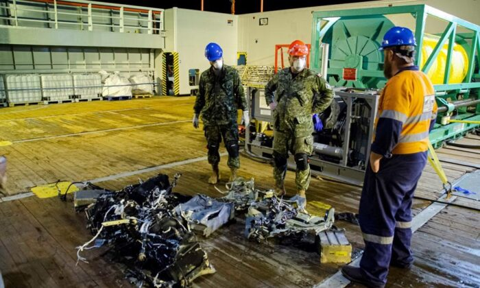 Canadian Forces members and EDT Hercules personnel inspect recovered parts of the helicopter Stalker 22 during recovery operations for the aircraft in the Mediterranean Sea on May 31, 2020. (The Canadian Press/HO-Department of National Defence, Cdr Robert Watt)