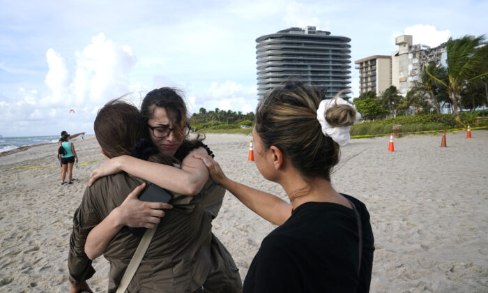 Faydah Bushnaq, of Sterling, Va., (C) is hugged by Maria Fernanda Martinez, of Boca Raton, Fla., as they stand outside of a 12-story beachfront condo building which partially collapsed, in the Surfside area of Miami, Fla., on June 25, 2021. (Lynne Sladky/AP Photo)