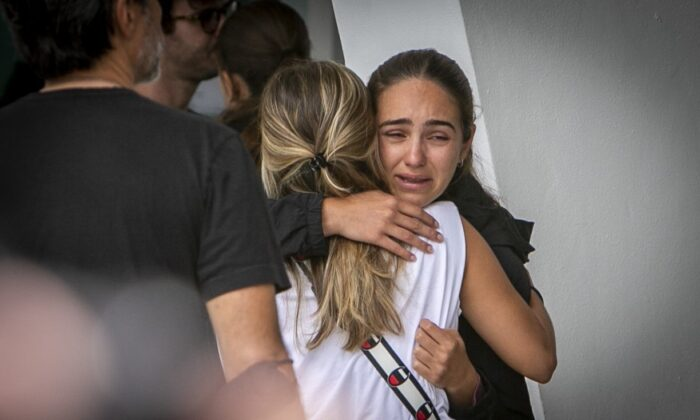 Two women comfort each other at the Surfside community center where friends and family of those missing following the collapse of a residential building  wait for new developments in the search for their loved ones, in Surfside, Fla., on June 25, 2021. (Jose A. Iglesias/Miami Herald via AP)