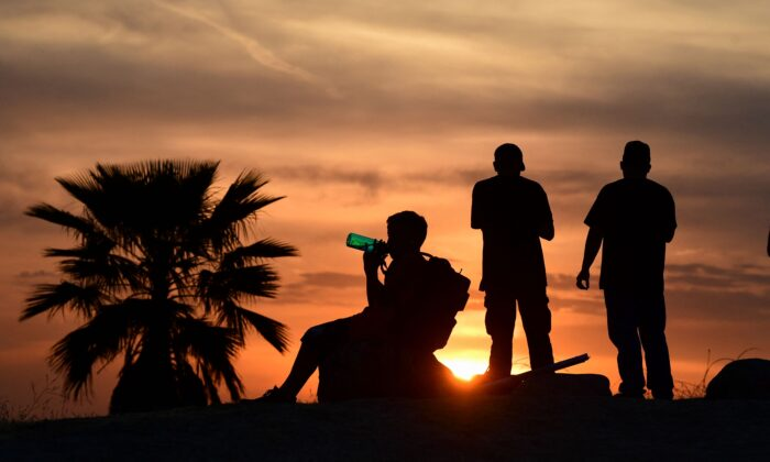 People view the sunset as a child drinks from a water bottle in Los Angeles, as temperatures soar in an early-season heatwave, Calif., on June 15, 2021. (Frederic J. Brown/AFP via Getty Images)