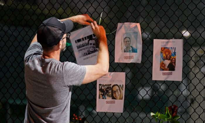 A man hangs a photo on a fence of someone missing near the site of an oceanfront condo building that partially collapsed in Surfside, Fla., on June 25, 2021. (Gerald Herbert/AP Photo)