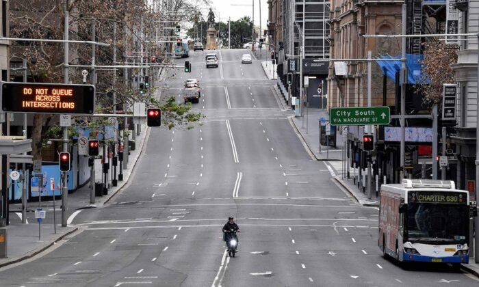 A food delivery worker rides in the central business district of Sydney as Australia's largest city entered a two-week lockdown to contain an outbreak of the highly contagious Delta variant on June 26, 2021. (Saeed Khan/AFP via Getty Images)