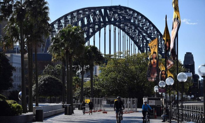 A couple ride along the harbour in Sydney on June 26, 2021, as Australia's largest city entered a two-week lockdown to contain an outbreak of the highly contagious Delta variant. (Saeed Khan/AFP via Getty Images)