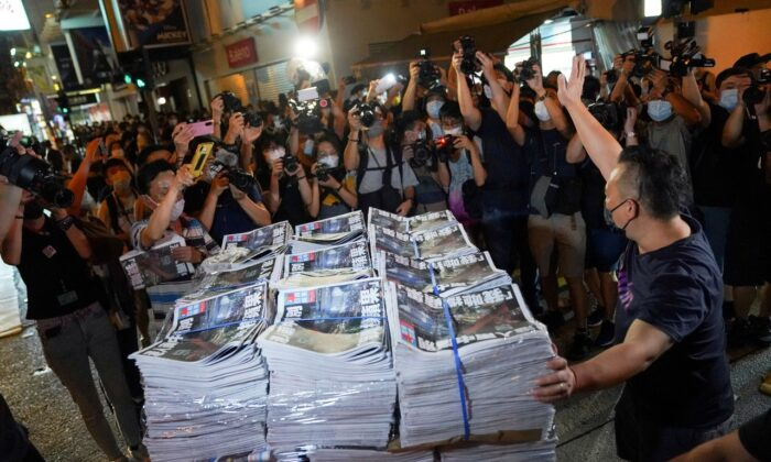 A man gestures as he brings copies of the final edition of Apple Daily, published by Next Digital, to a news stand in Hong Kong, on June 24, 2021. (Lam Yik/Reuters)