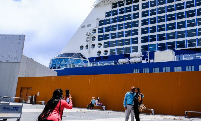 A woman takes a photo of a couple before the Celebrity Edge cruise ship in Fort Lauderdale, Fla., on June 26, 2021. (Maria Alejandra/AFP via Getty Images)