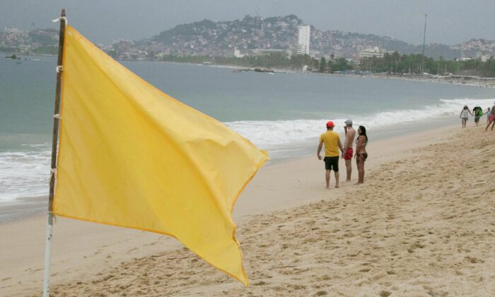 Tourists are pictured on Acapulco beach after storm Enrique became a hurricane off the coast of western Mexico, in Acapulco, Mexico, on June 26, 2021. (Javier Verdin/Reuters)