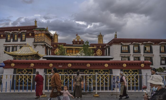 Tibetan Buddhists walk the kora in front of the Jokhang Temple, a UNESCO heritage site, on June 1, 2021 in Lhasa, Tibet region, China. Travel restrictions for foreign travelers were recently loosened in a bid to boost tourism to Tibet. The Chinese regime is aiming for 61 million visitors annually by 2025, more than 15 times the number of Tibets inhabitants. (Kevin Frayer/Getty Images)