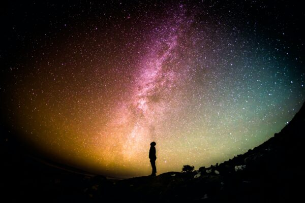 A person stands and looks up at the Milky Way at night