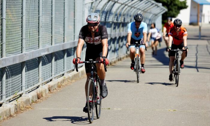 Bicyclists ride across a pedestrian bridge in the morning to escape from the heat in Portland, Ore., on June 27, 2021. (Craig Mitchelldyer/AP Photo)