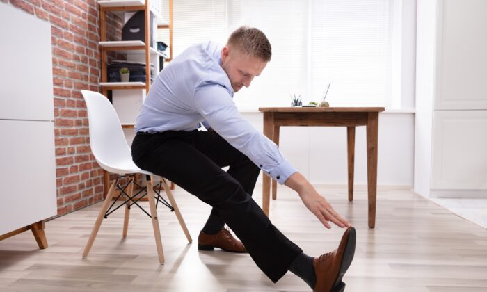 Chair stretching can include reaching for the sky with both arms, breathing, and twisting by turning your head to the right and torso to left. (Andrey_Popov/Shutterstock)